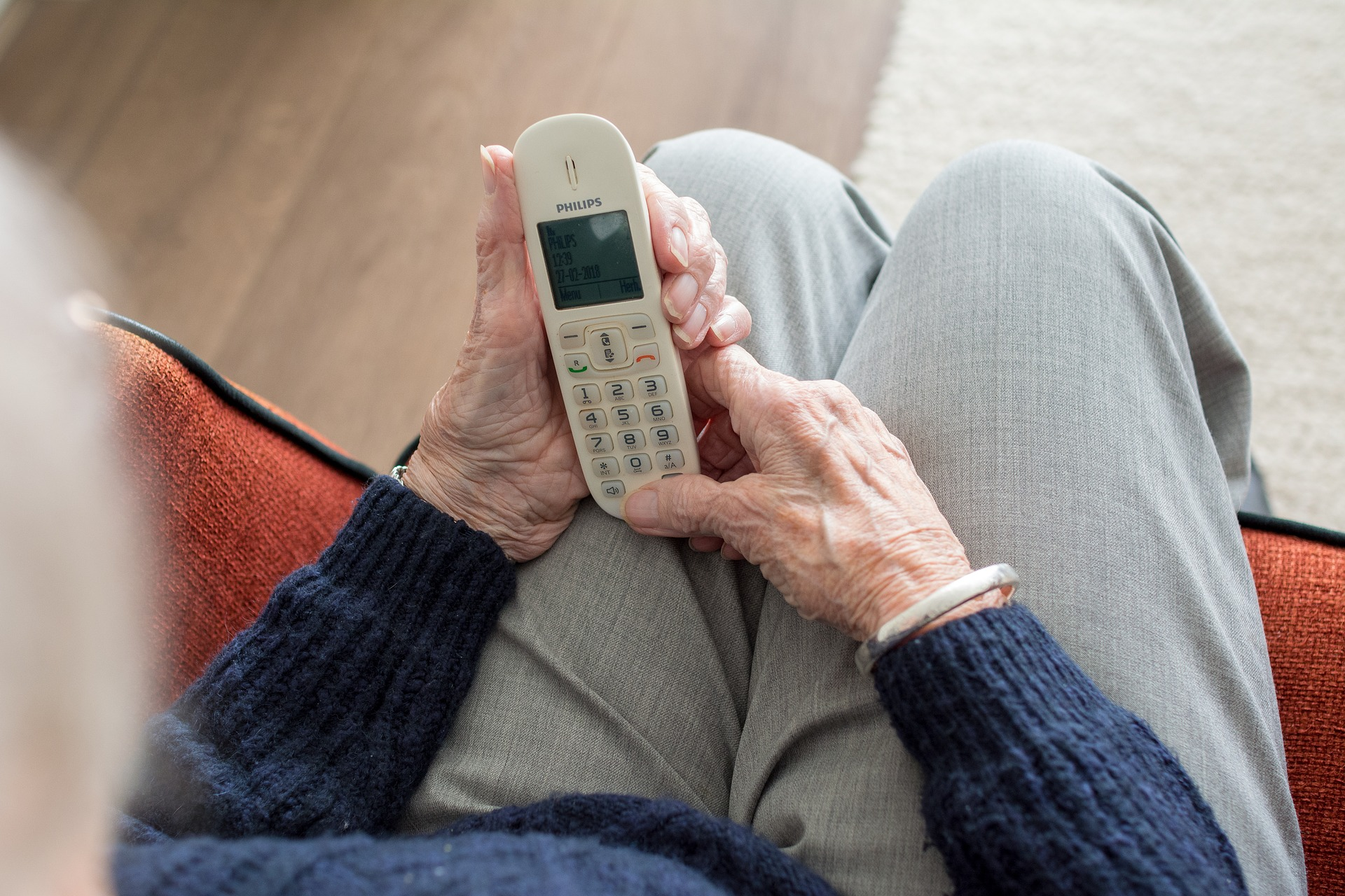 Photograph of older person sitting using home phone.